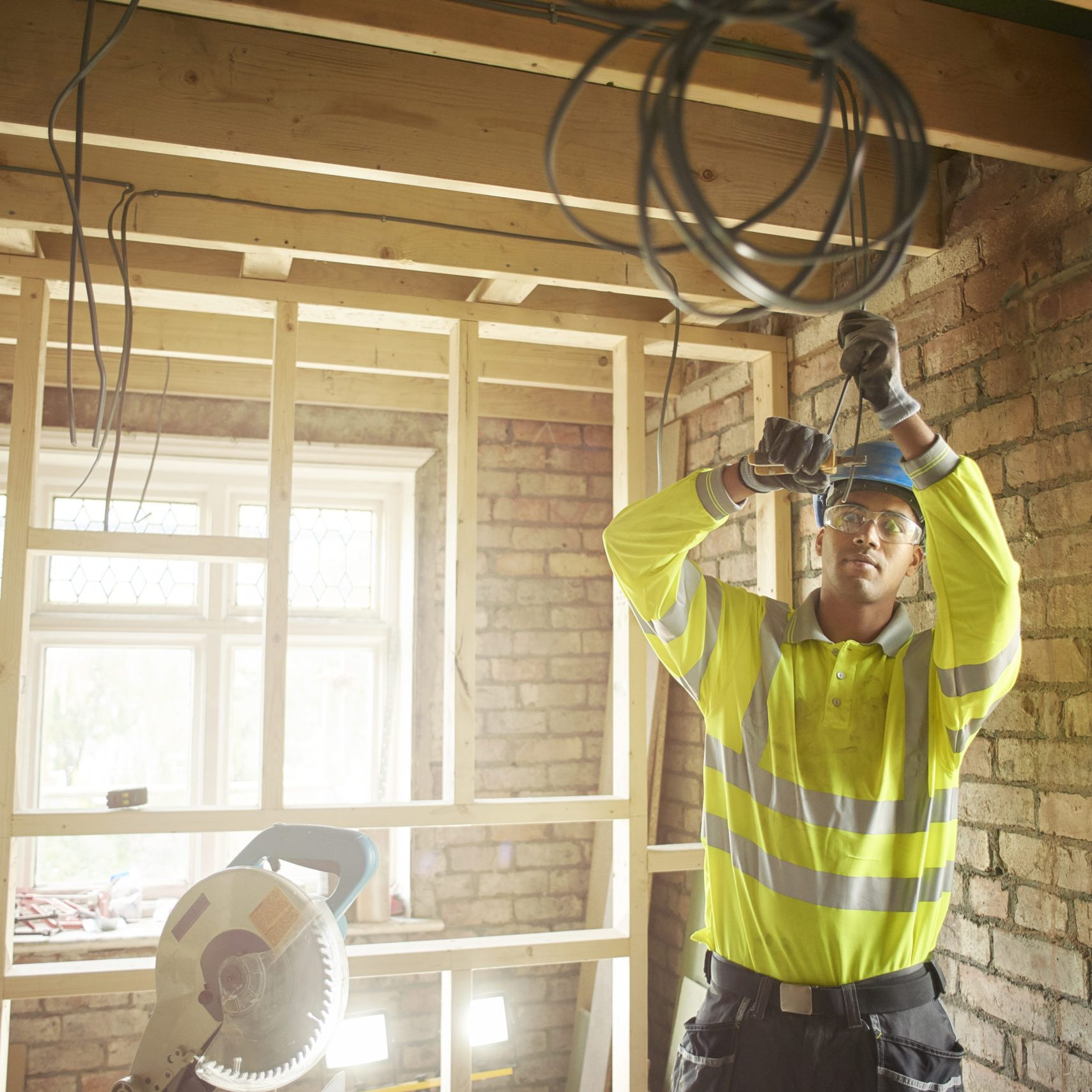 a young male carpenter clipping electrical wires on a first fix
